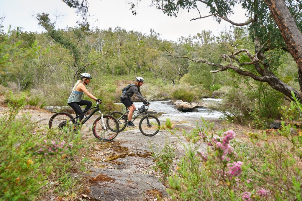 An image of a couple riding mountain bikes in a forest with river beside them shows outdoor adventure experiences immersed in nature while on The South West Edge road trip