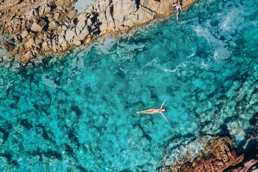 A drone image shows a woman floating in a pristine crystal clear rock pool to show natural attractions en route along The Edge road trip