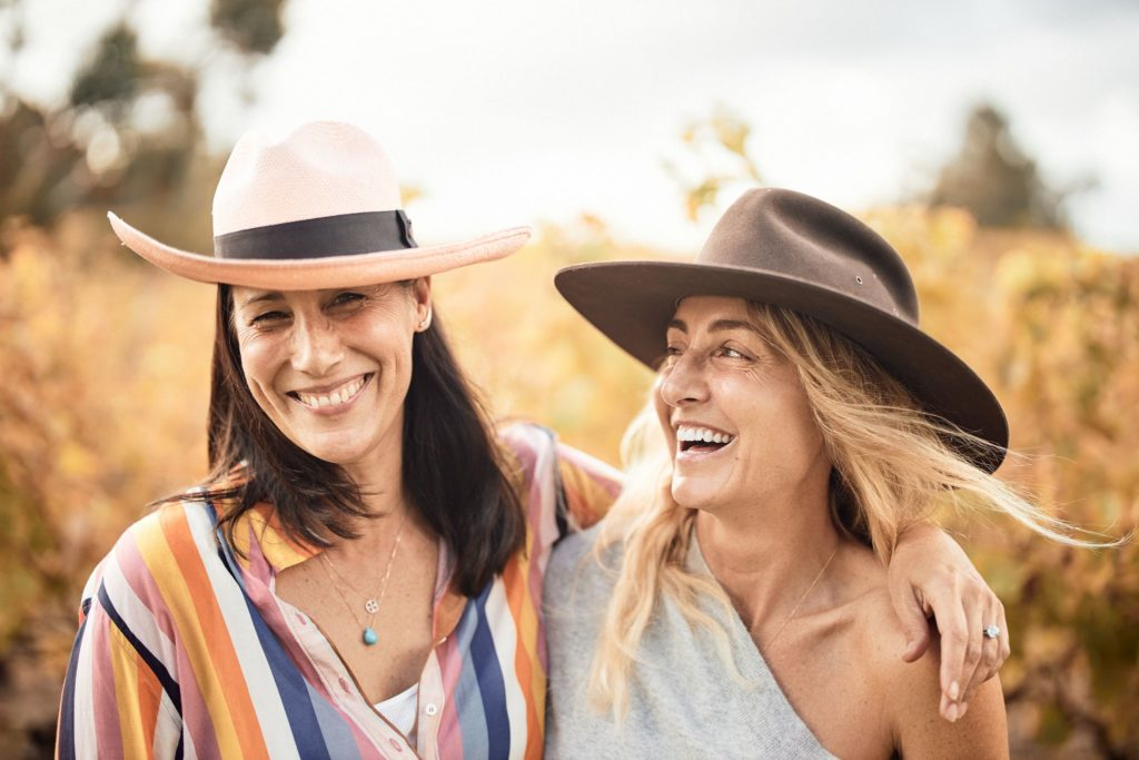 Two women smiling and laughing with a vineyard behind them shows happiness while travelling the south western australia road trip