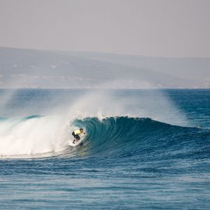 A man surfs a tunnel wave to show adventure activities to do on this road trip down south western australia