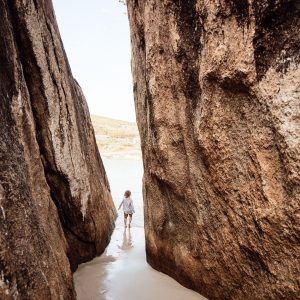 A small child walks through a thin walkway between two granite boulders on a beach to show the rugged natural landscape found on The South West Edge road trip in south west australia