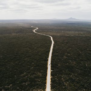 A drone shot of a long road and wide landscape with mountains in the distance